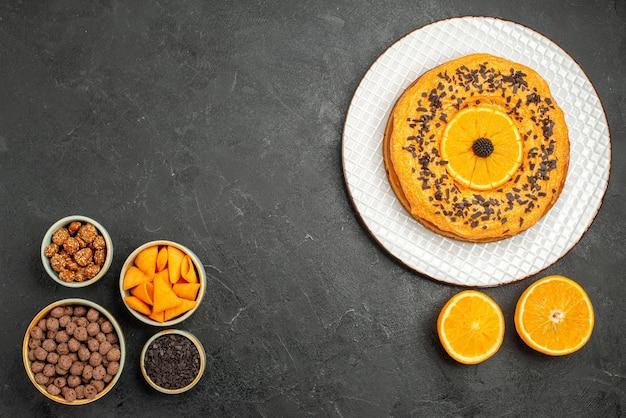 Widok z góry pyszne ciasto z plastrami pomarańczy na ciemnoszarej powierzchni słodkie ciastko z herbatnikami owocowymi i herbatą