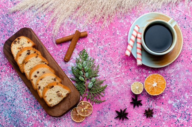 Widok z góry pyszne ciasto z rodzynkami pokrojone ciasto z filiżanką kawy na różowej powierzchni upiec ciasto z cukrem słodkie ciasteczka biszkoptowe