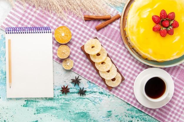 Widok z góry pyszne ciasto z żółtym syropem i filiżanką herbaty na jasnoniebieskiej powierzchni ciasto biszkoptowe słodkie ciasteczka ciasteczka cukrowa herbata