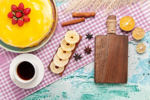 Widok z góry pyszne ciasto z żółtym syropem i filiżanką herbaty na niebieskiej powierzchni ciasto biszkoptowe słodkie ciasteczka z cukrem