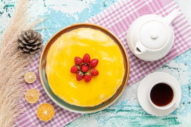 Widok z góry pyszne ciasto z żółtym syropem i świeżymi czerwonymi truskawkami na jasnoniebieskiej powierzchni ciasto biszkoptowe upiec słodką herbatę z ciasta cukrowego