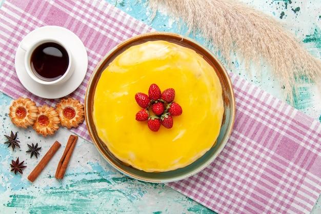 Widok z góry pyszne ciasto z żółtym syropem świeże czerwone truskawki i filiżankę herbaty na niebieskiej powierzchni ciasto biszkoptowe upiec słodki cukier
