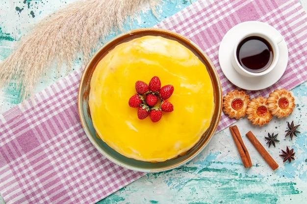 Widok z góry pyszne ciasto z żółtym syropem świeże czerwone truskawki i filiżankę herbaty na niebieskiej powierzchni ciasto biszkoptowe upiec słodkie ciasto cukrowe herbaciane ciastko