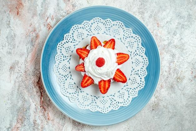 Widok z góry pyszne ciasto ze śmietaną i truskawkami na białej przestrzeni