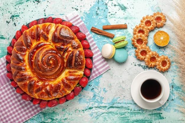 Widok z góry pyszne ciasto ze świeżymi czerwonymi truskawkami ciasteczka macarons i filiżanką herbaty na niebieskiej powierzchni