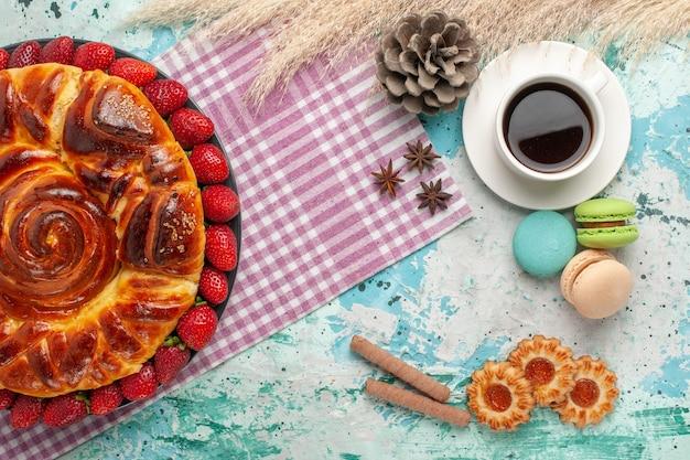 Widok z góry pyszne ciasto ze świeżymi czerwonymi truskawkami macarons i filiżanką herbaty na niebieskiej powierzchni