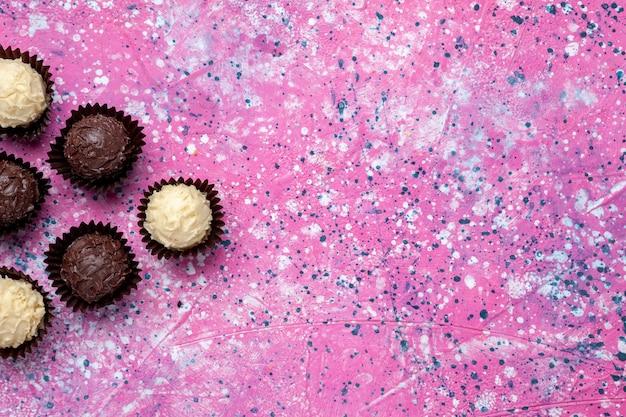 Widok z góry pyszne cukierki czekoladowe biała i ciemna czekolada na różowym biurku.