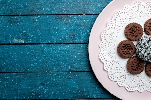 Widok z góry pyszne czekoladowe ciasteczka z ciastem czekoladowym na niebieskim biurku rustykalnym ciasto kakao herbata słodkie herbatniki