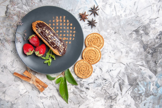 Widok z góry pyszne czekoladowe eklery z ciasteczkami na lekkim ciasteczkowym ciastku deserowym