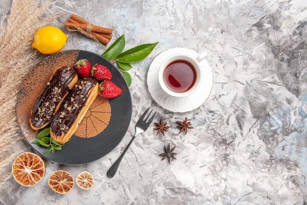 Widok z góry pyszne czekoladowe eklery z filiżanką herbaty na białym ciastku deserowym