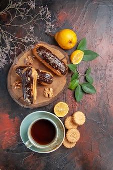 Widok z góry pyszne czekoladowe eklery z filiżanką herbaty na ciemnym stole słodkie ciasto deserowe