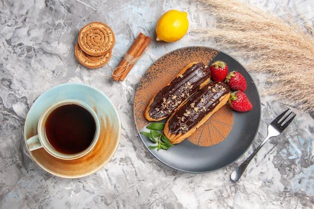 Widok z góry pyszne czekoladowe eklery z filiżanką herbaty na jasnym torcie z deserowymi ciasteczkami