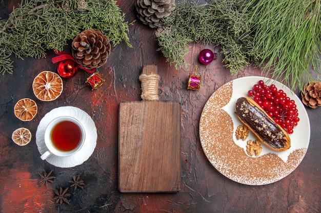 Widok z góry pyszne czekoladowe eklery z herbatą i jagodami na ciemnym stole słodkim tortem deserowym