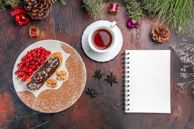 Widok z góry pyszne czekoladowe eklery z jagodami i herbatą na ciemnej podłodze ciasto deserowe słodkie