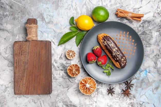 Widok z góry pyszne czekoladowe eklery z owocami na lekkim ciastku deserowym