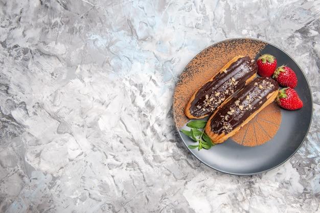 Widok z góry pyszne czekoladowe eklery z truskawkami na jasnej podłodze deserowe ciastko biszkoptowe