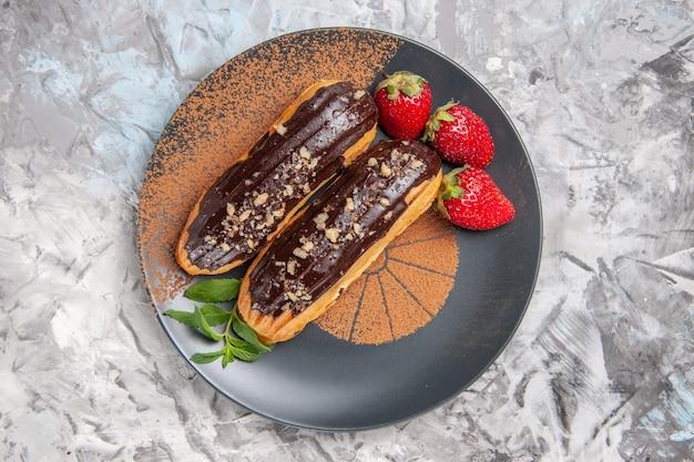 Widok z góry pyszne czekoladowe eklery z truskawkami na lekkim ciasteczku deserowym