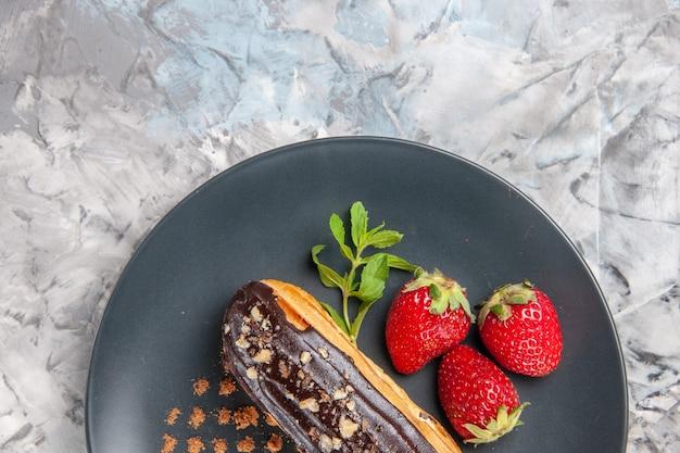 Widok z góry pyszne czekoladowe eklery z truskawkami na lekkim deserowym cieście cukierkowym