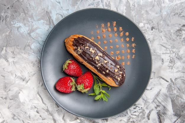Widok z góry pyszne czekoladowe eklery z truskawkami na lekkim deserowym cieście owocowym