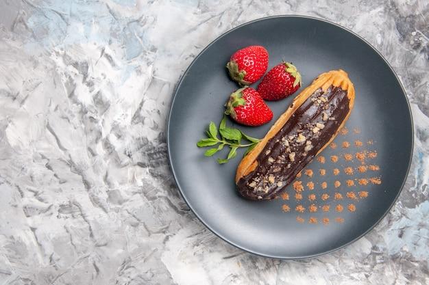 Widok z góry pyszne czekoladowe eklery z truskawkami na lekkim deserze z owocami