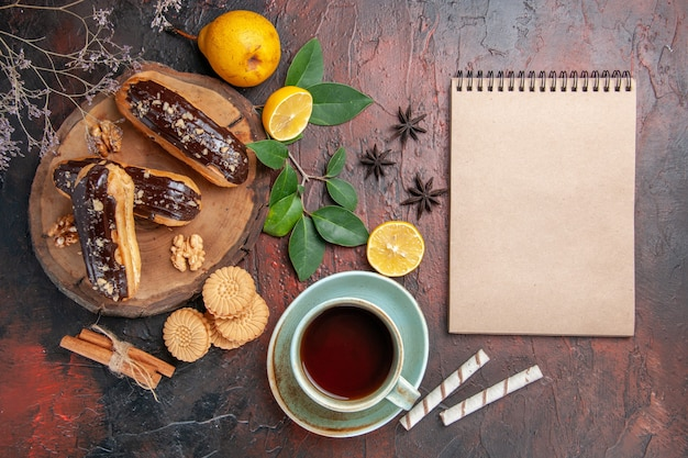 Widok z góry pyszne eklery choco z filiżanką herbaty na ciemnym stole deser słodycze ciasto