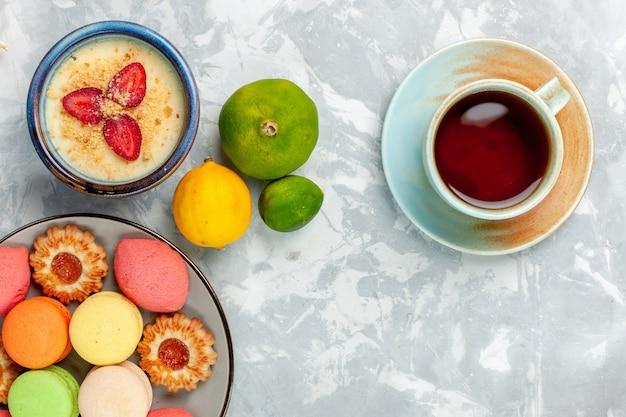 Widok z góry pyszne francuskie macarons z ciasteczkami deser i herbatą na jasnym białym tle piec ciasto herbatniki cukier słodkie zdjęcie