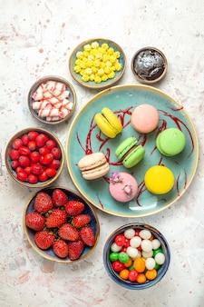 Widok z góry pyszne francuskie makaroniki z cukierkami i jagodami na białym słodkim biszkoptowym cieście
