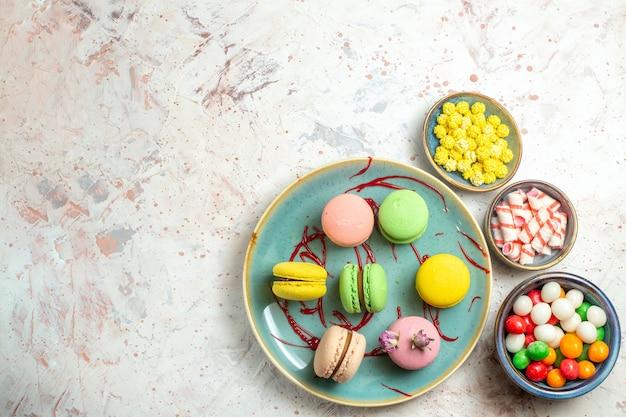 Widok z góry pyszne francuskie makaroniki z cukierkami na białym ciastku biszkoptowym