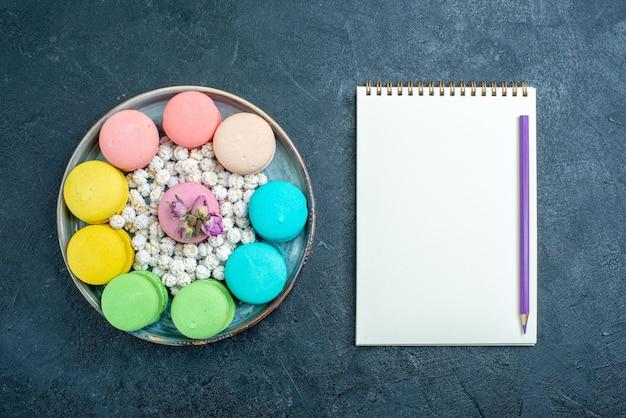 Widok z góry pyszne francuskie makaroniki z cukierkami wewnątrz tacy na ciemnym biurku