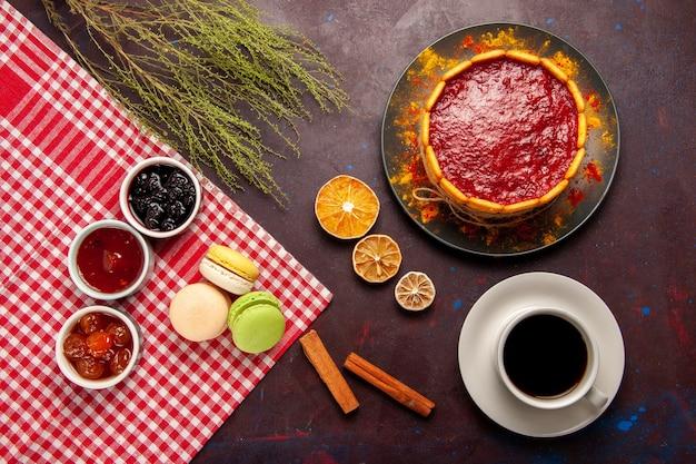 Widok z góry pyszne francuskie makaroniki z dżemami owocowymi i filiżanką kawy na ciemnej powierzchni słodkie ciasto owocowe herbatniki słodkie ciasteczko cukrowe