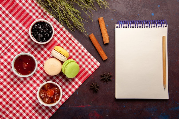 Widok z góry pyszne francuskie makaroniki z dżemami owocowymi na ciemnym biurku dżem słodka herbata ciastko biszkoptowe słodkie