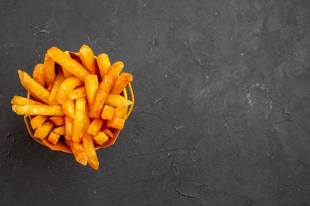 Widok z góry pyszne frytki wewnątrz opakowania na ciemnym tle fast-food danie ziemniaczane burger posiłek