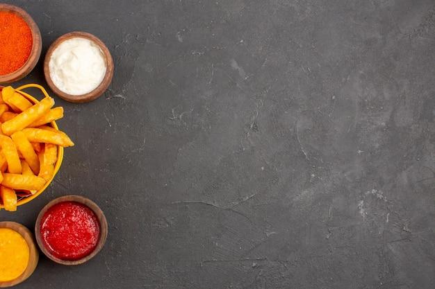 Widok z góry pyszne frytki z sosami na ciemnym naczyniu na biurko burger fast food ziemniaczany posiłek