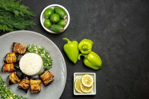 Widok z góry pyszne gotowane bakłażany z ryżową cytryną i feijoa na ciemnej podłodze obiad jedzenie olej do gotowania ryżowy posiłek