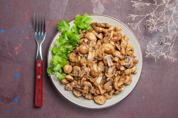 Widok z góry pyszne gotowane grzyby z zieleniną na ciemnym tle jedzenie dziki obiad roślinny posiłek