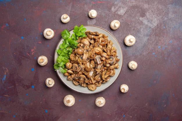Widok z góry pyszne gotowane grzyby z zieleniną w ciemności