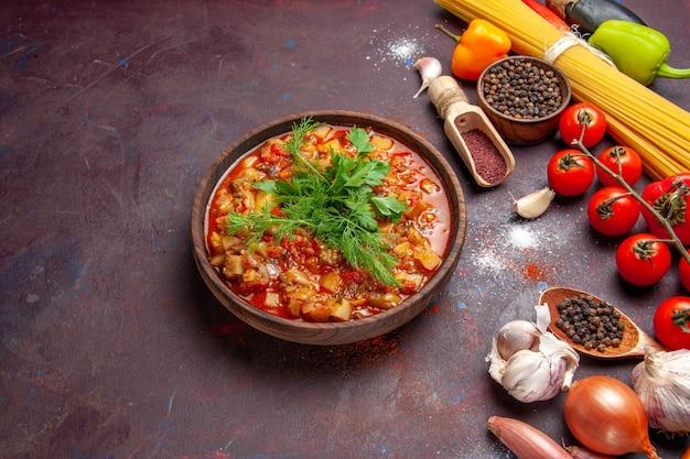 Widok z góry pyszne gotowane warzywa pokrojone w plasterki z zieleniną i przyprawami na ciemnym stole z sosem z zupy