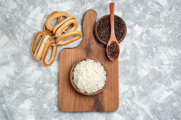 Widok z góry pyszne gotowany ryż z przyprawami i słodkimi krakersami na białym tle