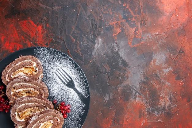 Widok z góry pyszne herbatniki rolki wewnątrz płyty na ciemnym tle