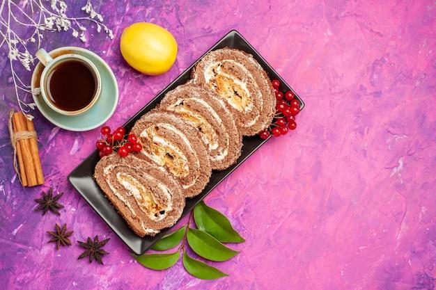 Widok z góry pyszne herbatniki z filiżanką herbaty na różowym tle