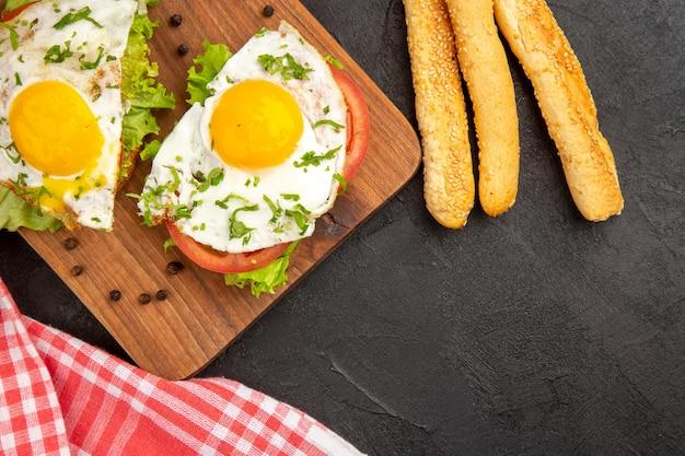 Widok z góry pyszne kanapki z jajkiem i chlebem na ciemnym tle posiłek chleb obiad gotować omlet jedzenie śniadanie jajko
