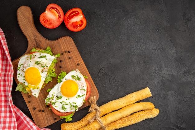 Widok z góry pyszne kanapki z jajkiem i chlebem na ciemnym tle posiłek chleb obiad jajko gotować omlet jedzenie śniadanie