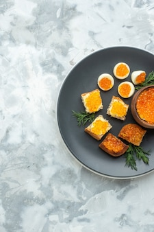 Widok z góry pyszne kanapki z kawiorem z gotowanymi jajkami wewnątrz talerza białe tło śniadanie jedzenie posiłek owoce morza ryba obiad chleb