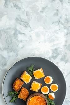 Widok z góry pyszne kanapki z kawiorem z gotowanymi jajkami wewnątrz talerza białe tło śniadanie jedzenie posiłek owoce morza ryba obiad tosty