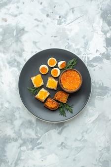 Widok z góry pyszne kanapki z kawiorem z gotowanymi jajkami wewnątrz talerza białe tło śniadanie jedzenie posiłek ryba obiad tost chleb