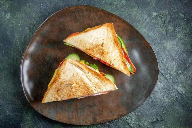 Widok z góry pyszne kanapki z szynką wewnątrz ciemnej powierzchni talerza
