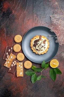 Widok z góry pyszne kremowe ciasta z ciasteczkami na ciemnym stole słodkie ciasto deserowe
