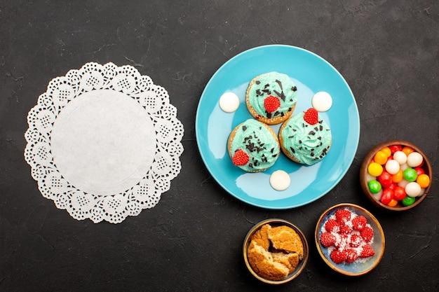 Widok z góry pyszne kremowe ciasta z cukierkami na ciemnym tle ciasto deserowe ciasteczka cukierkowe ciasteczka kolor