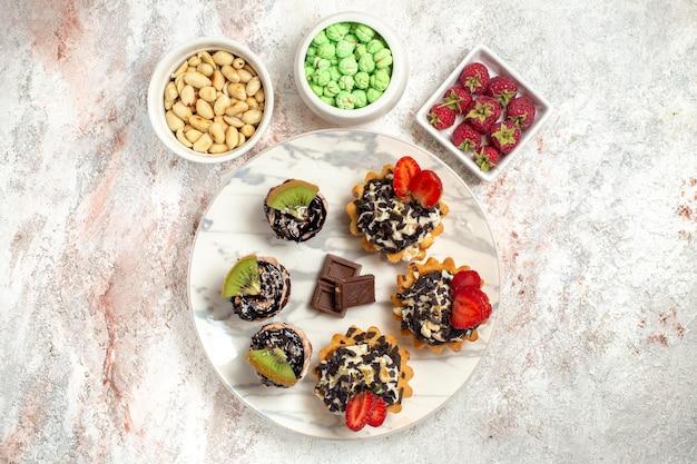Widok z góry pyszne kremowe ciasta z orzechami i cukierkami na białej powierzchni