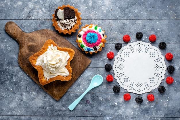 Widok z góry pyszne kremowe ciasto w kształcie gwiazdy z ciasteczkami jagodowymi i niebieską łyżką na jasnym tle ciasto biszkoptowe krem słodka herbata